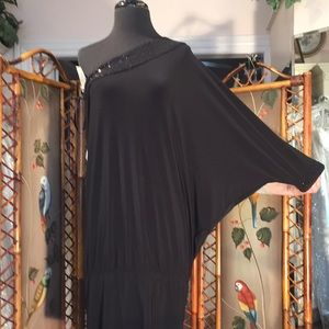 Bat wing single shoulder form fitting black dress.